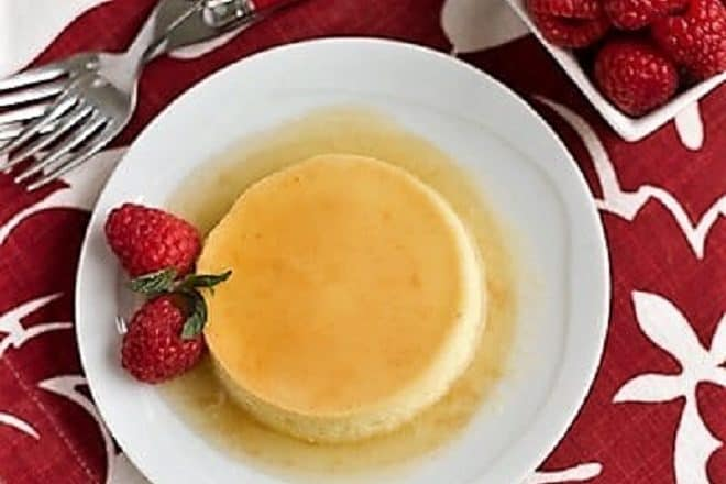 Classic Flan on a white dessert plate garnished with raspberries and mint