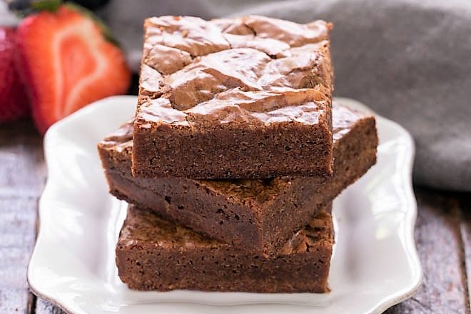 3 fudgy homemade Brownies stacked on a square white plate