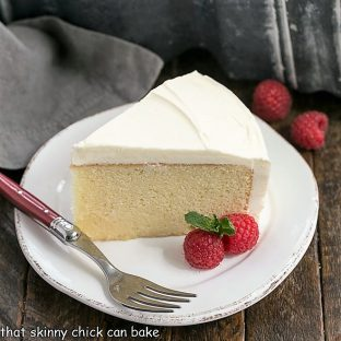Slice of vanilla cake on a round dessert plate with two raspberries and a red handled fork