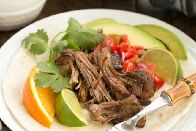 Slow cooked Pork Carnitas over a tortilla on a white plate