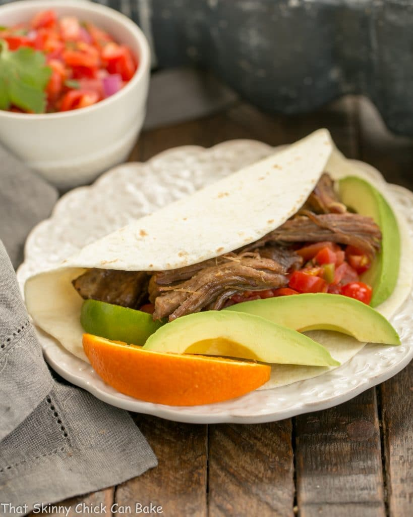 Slow cooked Pork Carnitas in a tortilla on a white plate with avocado and orange garnishes
