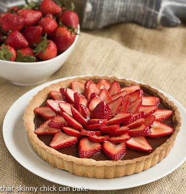 Strawberry Topped Chocolate Tart on a white plate with a bowl of strawberries