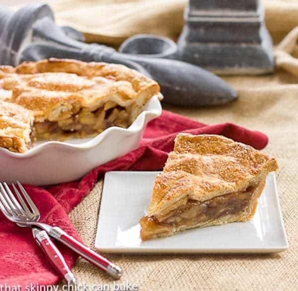 Classic Apple Pie slice on a square white plate with forks and a red napkin