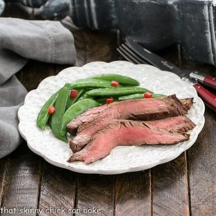 Korean grilled flank steak and sugar snap peas on a white dinner plate