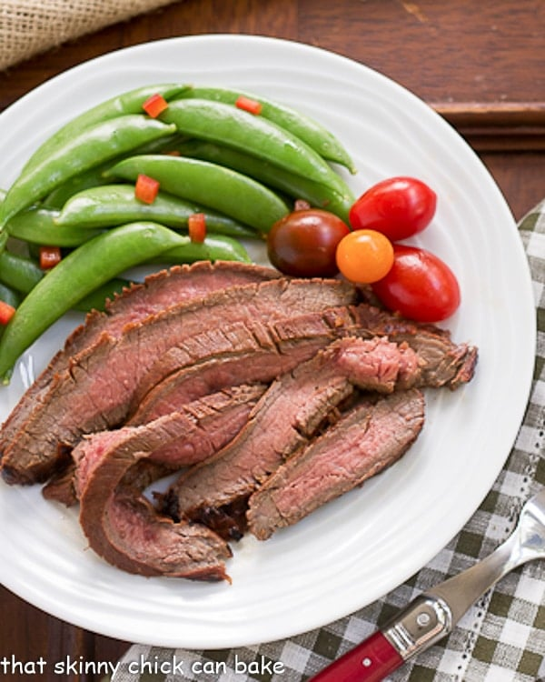 Korean Grilled Flank Steak slices on a white plate with sugar snap peas and grape tomatoes