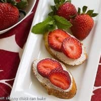 Overhead view of strawberry goat cheese tartines on a white tray garnished with mint and strawberries