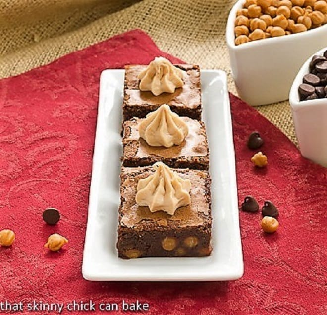 Fudgy Caramel Brownies lined up on a dessert plate topped with piped caramel frosting