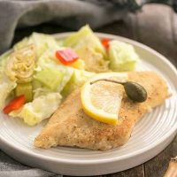 Easy Skillet Chicken Piccata on a round white plate with a lettuce salad