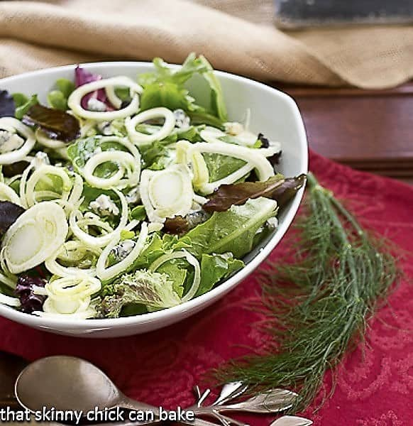 Fennel and Gorgonzola Salad in a white salad bowl in a serving bowl with a fennel frond