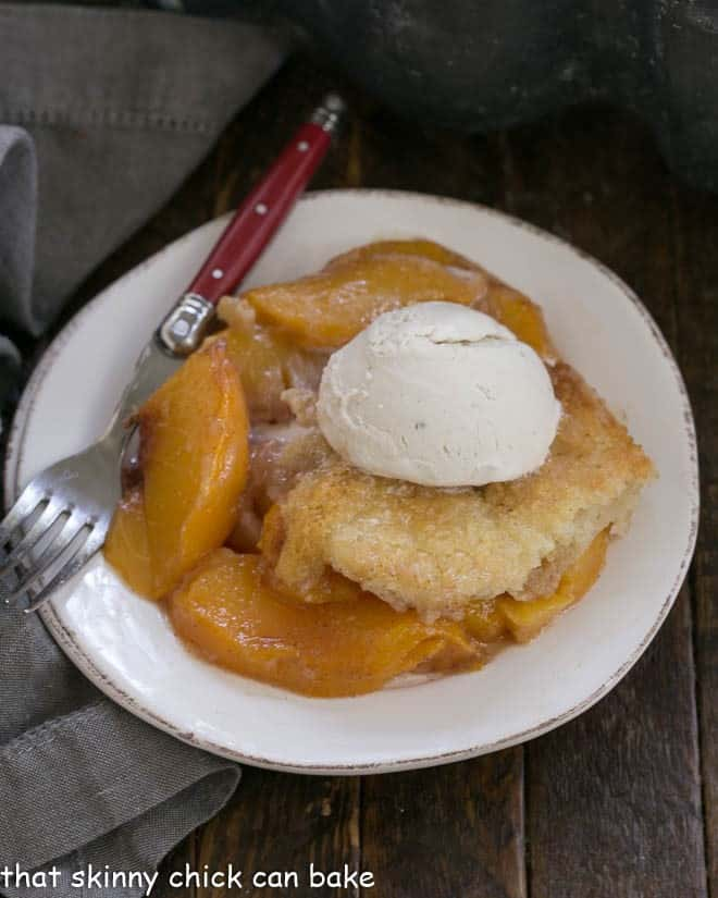 Overhead view of a scoop of easy peach cobbler on a white plate with scoop of vanilla ice cream