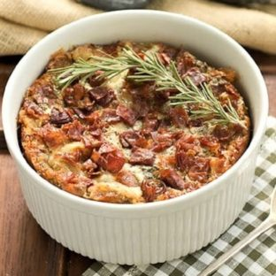 Prosciutto, Gorgonzola and Rosemary Strata in a round casserole dish with a sprig of rosemary to garnish