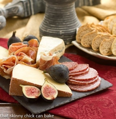A slate cheese board topped with meat and cheeses on a red napkin