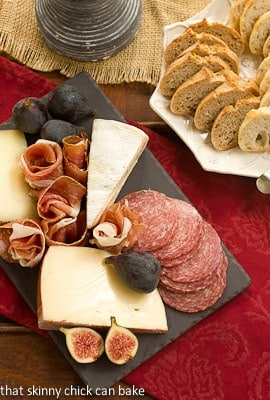 Overhead view of a meat and cheese tray  next to a plate of bread