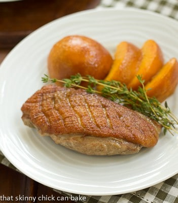 Seared Duck Breasts with peaches and thyme on a white dinner plate