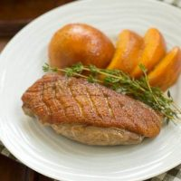 Seared Duck Breasts with peaches on a white dinner plate