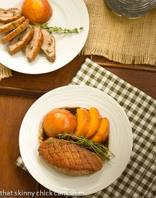 Seared Duck Breasts with peaches overhead view on white dinner plates with a checked napkin