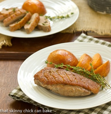 Seared Duck Breasts with Peaches on a white dinner plate with a sprig of fresh thyme
