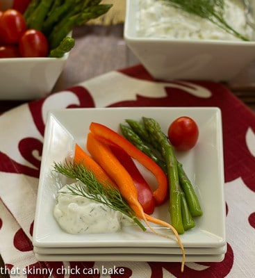 Tzatziki on a stack of white plates with fresh vegetables