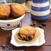 Sour Cream Blueberry Muffins on a white ceramic plate with the paper wrapper removed