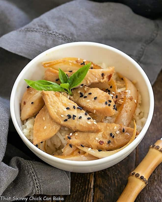 Easy chicken bulgoge in a white bowl garnished with a sprig of basil