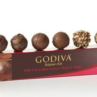 A Godiva chocolate box topped with an assortment of truffles