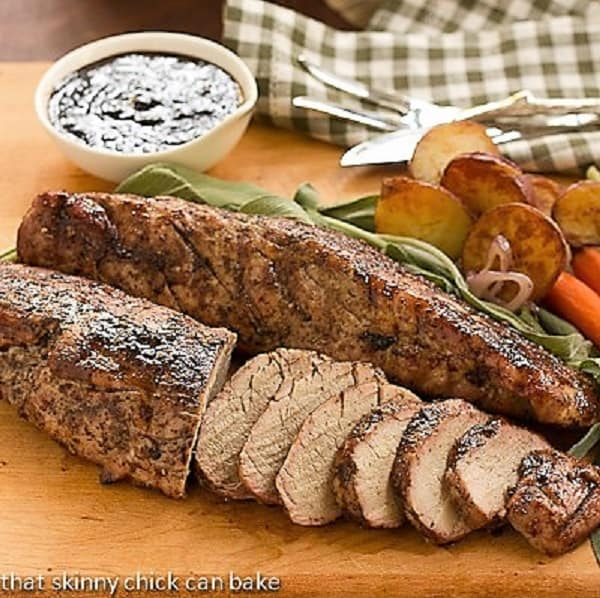 Sliced Grilled Pork Tenderloin with Plumb Sauce on a cutting board