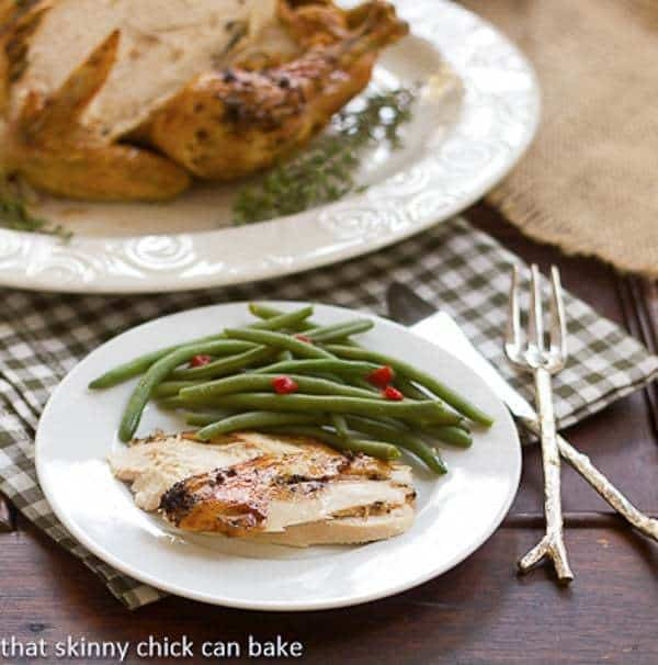 Slices of Roast Psycho Chicken on a white plate with green beans