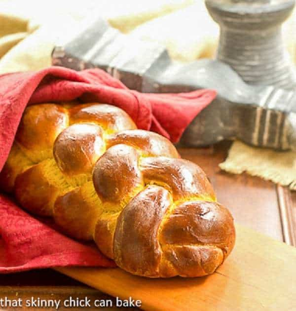 Pumpkin Challah wrapped in a red napkin on a cutting board