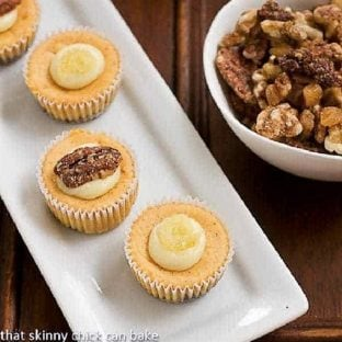 Mini Pumpkin Cheesecakes on a white serving tray next to a bowl of pecans