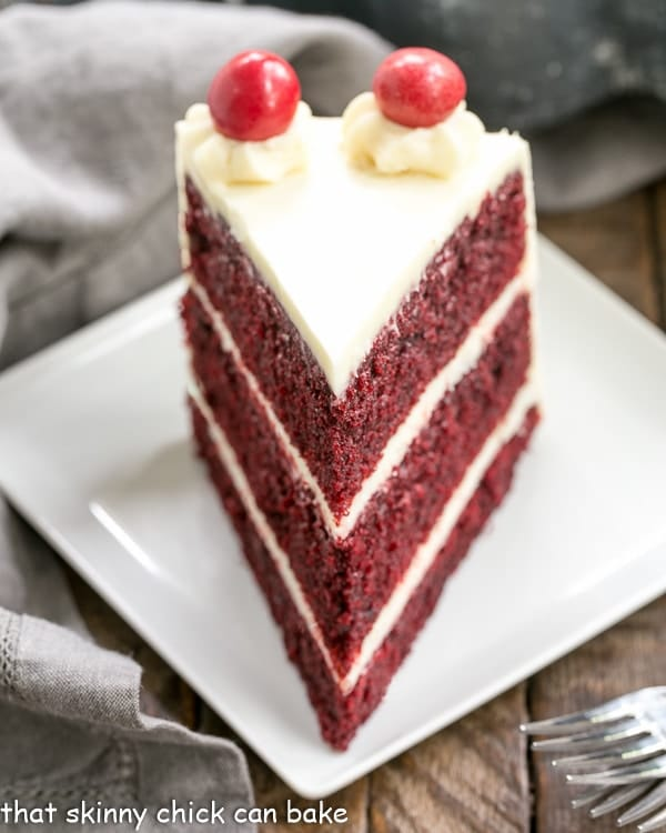 Red Velvet Cake with White Chocolate Cream Cheese Frosting slice on a white plate