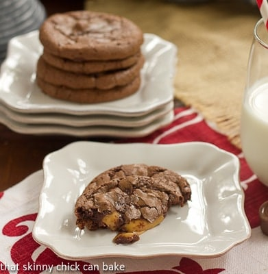 Stack of Rolo Brownie Cookie in the background with one partial cookie with gooey caramel oozing out on a white plate in the foreground