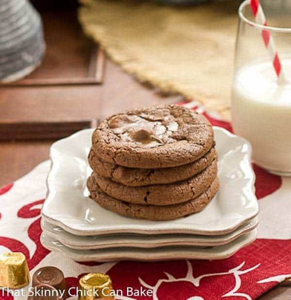 Rolo Brownie Cookies stacked on 4 white dessert plates