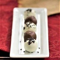 Oreo Truffles lined up on a white ceramic platter