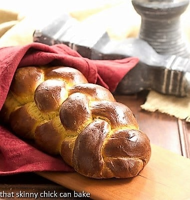 Pumpkin challah loaf wrapped in a red napkin