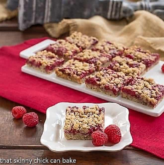 Raspberry Streusel Bars on a white tray with one bar on a dessert plate in front with a fresh raspberry garnish
