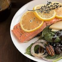 Overhead view of salmon garnished with lemon on a dinner plate with a spinach salad