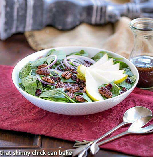 Spinach Salad with Pears, Cranberries and Candied Pecans in a white serving bowl sitting on a red napkin with silver serving utensils