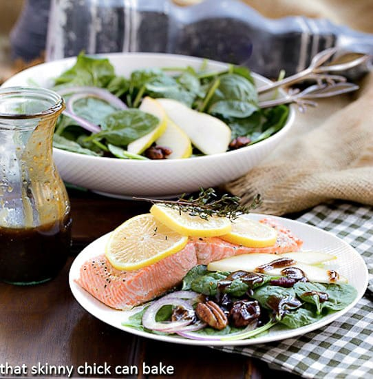Spinach Salad with Pears, Cranberries and Candied Pecans on a white plate with a salmon fillet