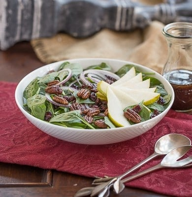 Spinach salad with pears cranberries and candied pecans in a white ceramic bowl