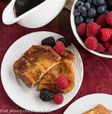 Overhead view of Sugar-Crusted French Toast on a white ceramic plate with fresh berries