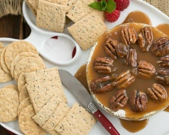 cheese tray with a wheel of baked Camembert topped with caramel sauce and pecans