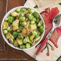 Brussels Sprouts with Bacon, Shallots and Garlic in a white bowl with a red handled spoon