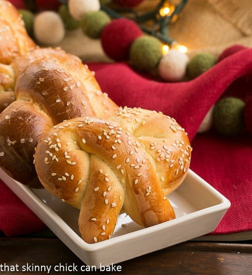 Homemade Challah Pretzels covered with sesame seeds on a white try