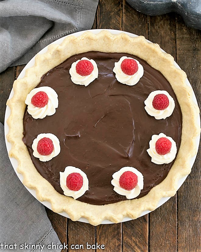 Overhead view of Chocolate Pie in a white pie dish topped with cream and berries