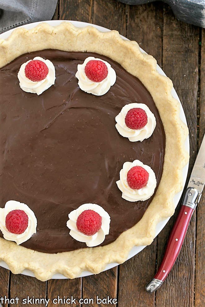 Overhead view of a chocolate cream pie with a red handled knife