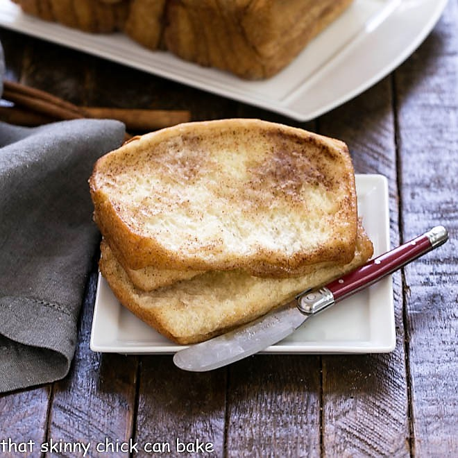 2 slices of cinnamon pull apart bread on a white plate with a red handle knife