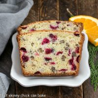 Two slices of cranberry orange bread on a square white plate