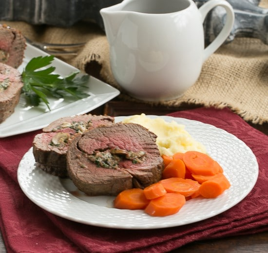 Gorgonzola and Mushroom Stuffed Beef Tenderloin  on a dinner plate with carrots and mashed potatoes