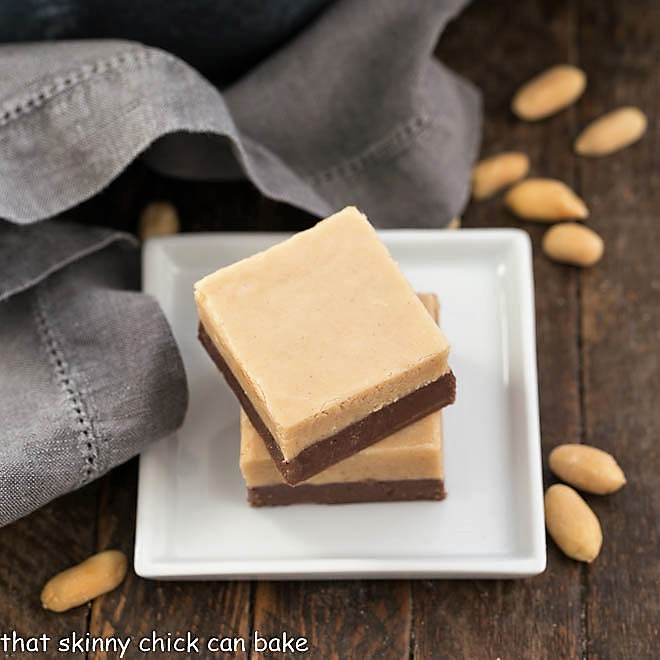 Two slices of Layered Chocolate Peanut Butter Fudge on a square white plate