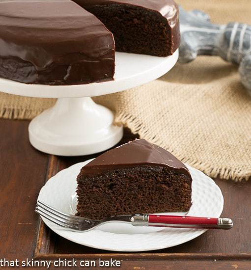 One Layer Fudge Cake with a rich chocolate ganache topping on a white dessert plate